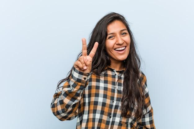 勝利のサインを示し、広く笑っている若いクールなインドの女性。