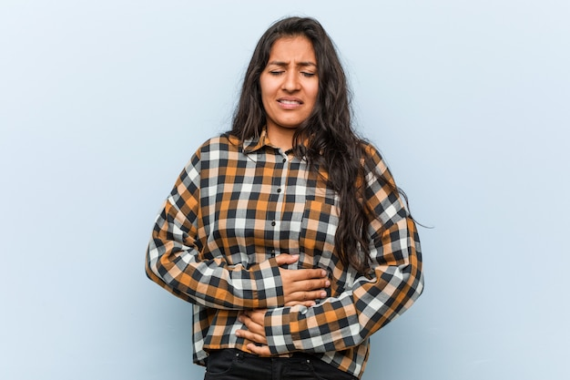 Young cool indian woman sick, suffering from stomachache, painful disease concept.