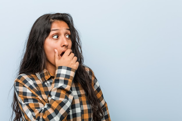 Young cool indian woman thoughtful looking to a copy space covering mouth with hand.