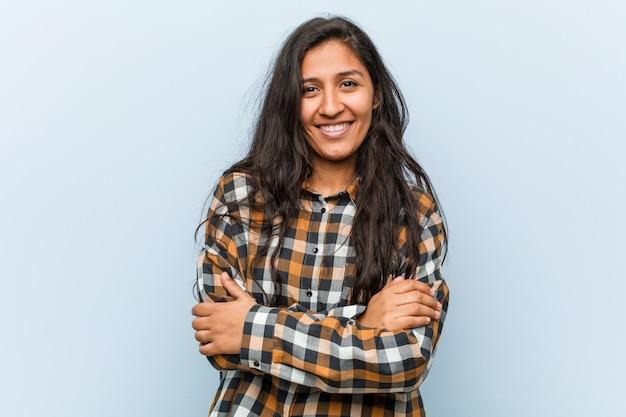 Молодая спокойная индийская женщина, которая чувствует себя уверенно, скрестив руки с решимостью