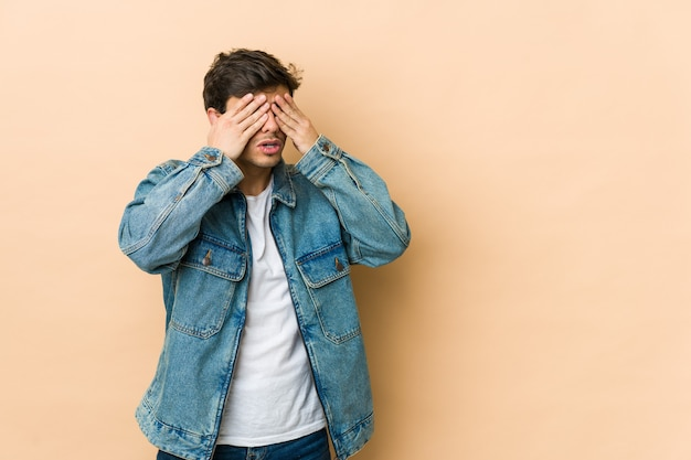 Young cool man afraid covering eyes with hands