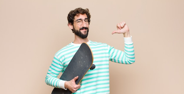 Young cool man bearded with a skate board