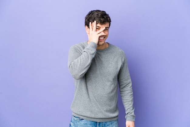 Young cool man blink through fingers, embarrassed covering face.