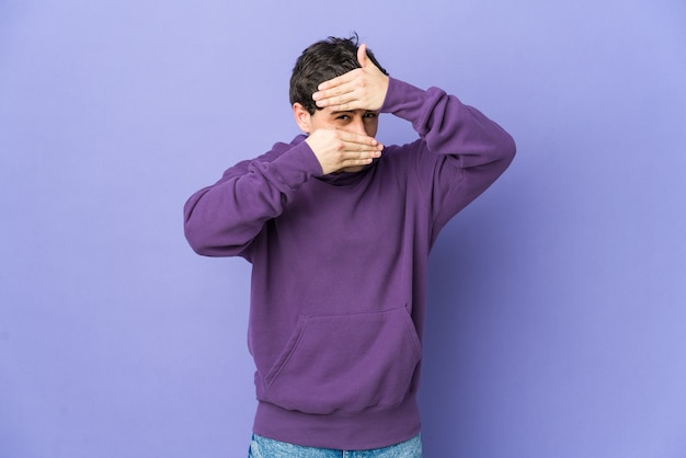 Young cool man blinking through fingers, embarrassed covering face