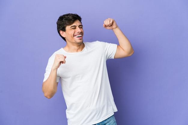 特別な日を祝う若いクールな男は、エネルギーでジャンプして腕を上げます。
