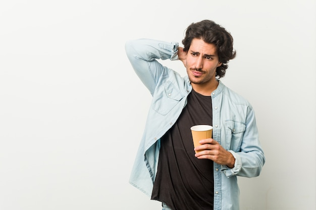 Young cool man drinking a coffee touching back of head, thinking and making a choice.