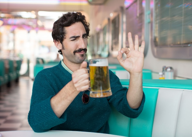 Young cool man drinking a pint of beer into an american dinner restaurant
