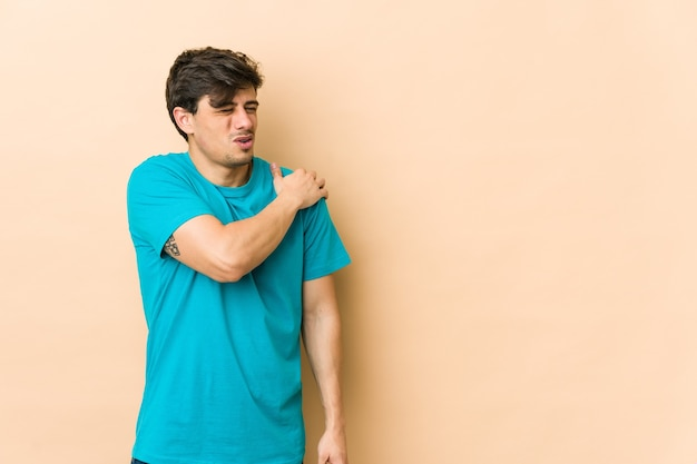 Young cool man having a shoulder pain.