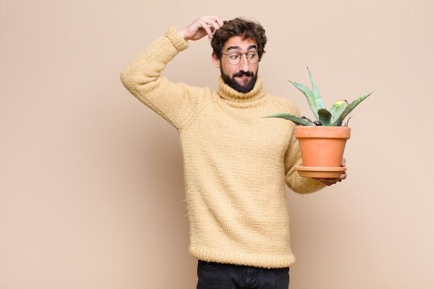 Молодой спокойный человек, держащий кактус