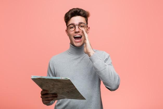 Молодой спокойный человек, держащий карту, весело улыбаясь, указывая указательным пальцем.