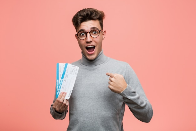 Young cool man holding an air tickets surprised pointing at himself, smiling broadly.
