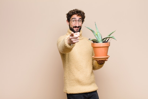 Young cool man holding a cactus plant against flat wall