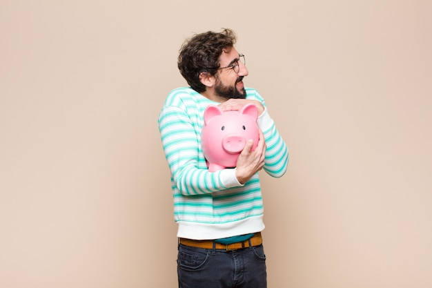 Young cool man holding a piggy bank against clean wall