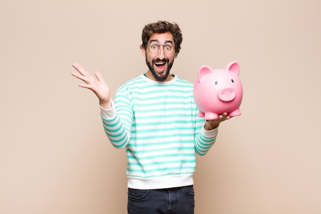 Young cool man holding a piggy bank on clean wall