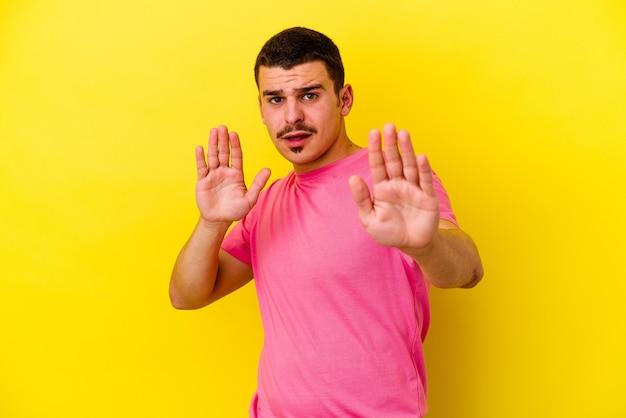 Молодой крутой мужчина изолирован на желтой стене в шоке из-за неминуемой опасности