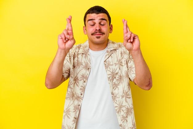 Молодой крутой мужчина изолирован на желтой стене, скрестив пальцы за удачу