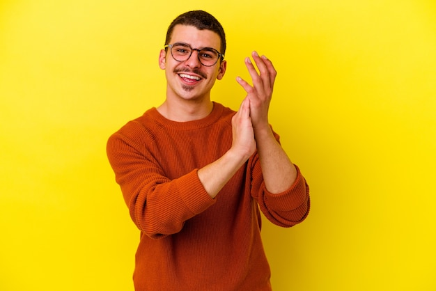 노란색 벽에 고립 된 젊은 멋진 남자는 정력적이고 편안한 느낌, 손을 문지르는 자신감