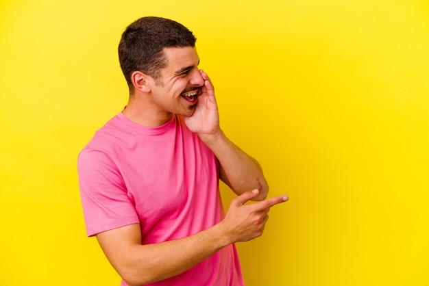 Молодой крутой мужчина изолирован на желтой стене, сплетничает, указывая на сторону, сообщая что-то