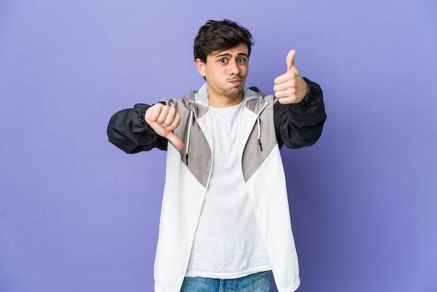 엄지 손가락과 엄지 손가락을 보여주는 멋진 젊은이, 어려운 개념 선택