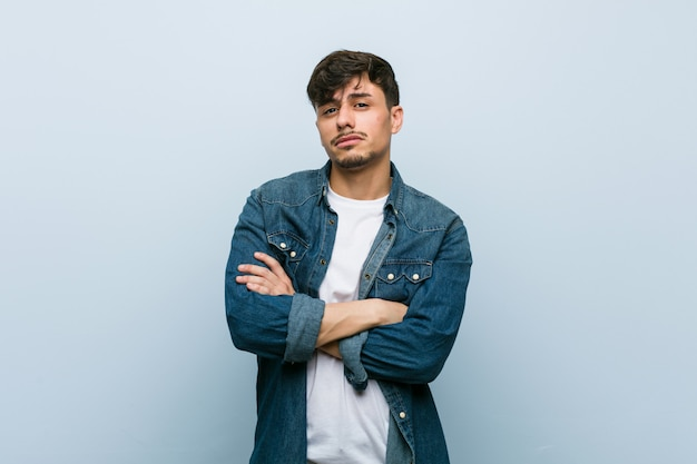 Young cool man unhappy looking in camera with sarcastic expression