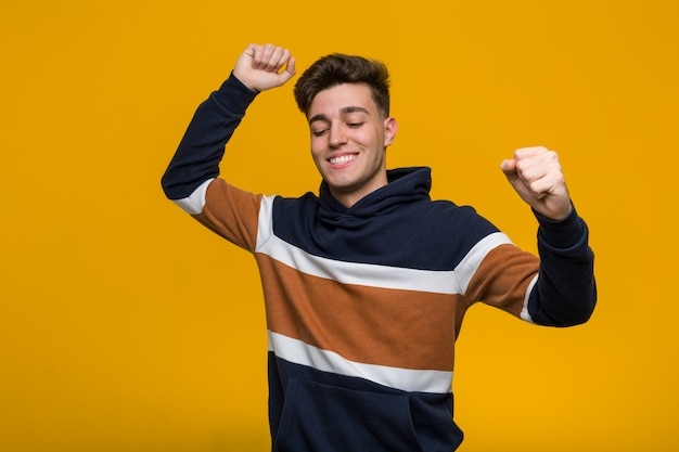 Young cool man wearing a hoodie celebrating a special day, jumps and raising arms with energy.