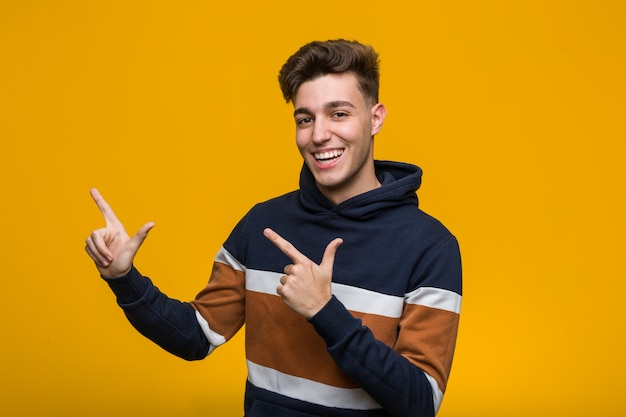 Young cool man wearing a hoodie pointing with forefingers to a copy space, expressing excitement and desire.