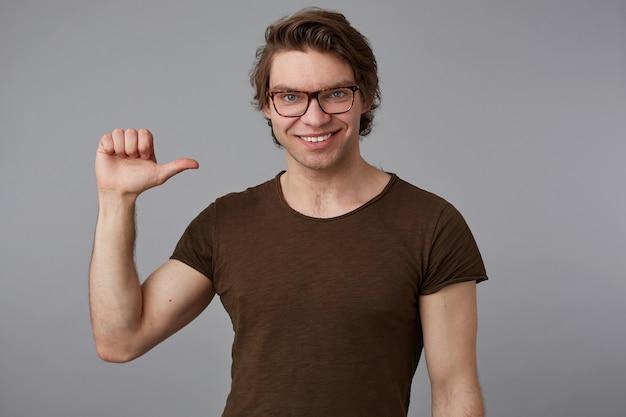 안경을 쓴 멋진 젊은이는 회색 배경 위에 서서 자신을 가리키는 공백 티셔츠를 입고 밝고 넓게 미소 짓습니다.