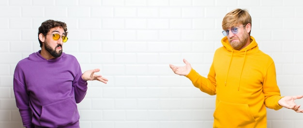 Young cool men looking puzzled, confused and stressed, wondering between different options, feeling uncertain on white tiles wall