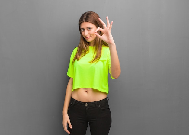 若いクールなロシアの女の子は陽気で自信を持ってokジェスチャーをしています