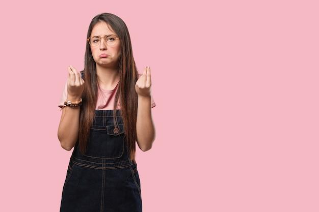 Молодая спокойная женщина делает жест необходимости