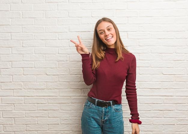 Молодая классная женщина над кирпичной стеной делает жест победы