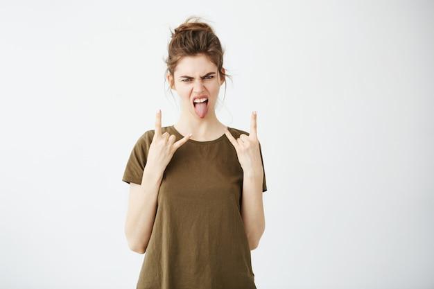 Молодая спокойная женщина при плюшка показывая язык и знак утеса.