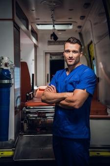 若い下士官は笑顔を保ち、背景の救急車の上に立っています。