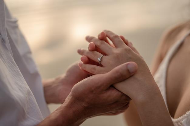 若いカップルがsunsetsummerinlovevalentineのビーチでガールフレンドと結婚する