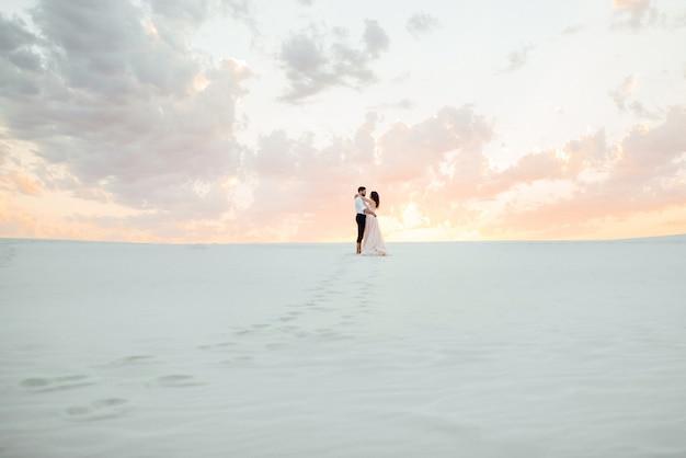젊은 부부는 검은 바지를 입은 남자와 분홍색 드레스를 입은 소녀가 사막의 하얀 모래를 따라 걷고 있습니다.