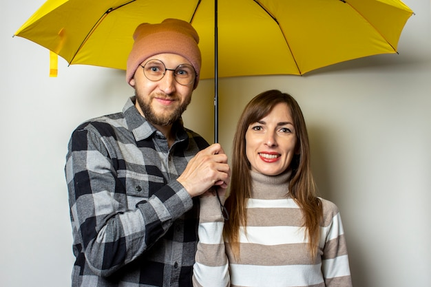 若いカップル、帽子のひげと格子縞のシャツの男とセーターの女の子が孤立した光の黄色い傘の下で笑っています。