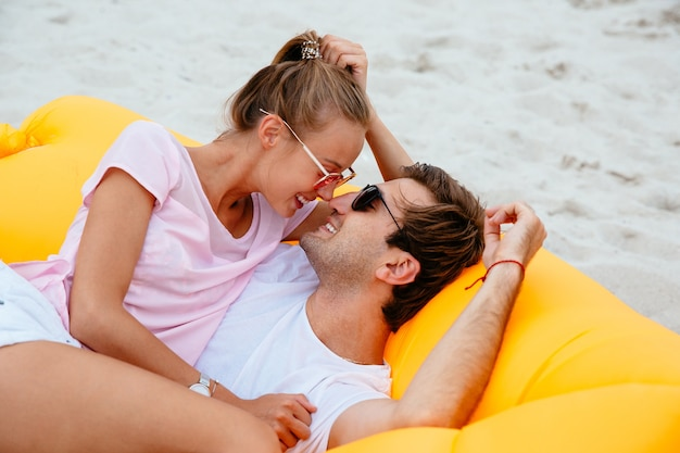Young couple admire while looking to each other, laying on yellow air sofa lamzac