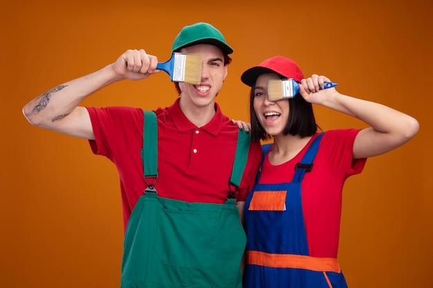 Giovane coppia ragazzo aggressivo ragazza gioiosa in uniforme da operaio edile e cappuccio che tiene il pennello davanti all'occhio ragazza che tiene la mano sulla spalla del ragazzo