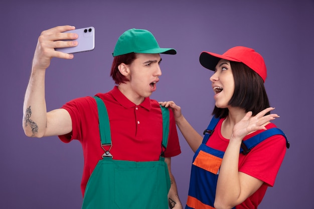 Giovane coppia infastidita ragazzo eccitato ragazza in uniforme operaio edile e berretto prendendo selfie insieme guardando l'altro ragazza tenendo la mano sulla spalla di ragazzi che mostra la mano vuota