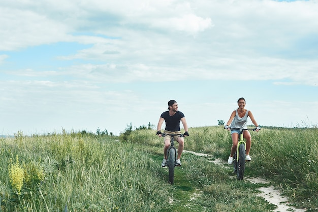Young couple are cycling at the green hills front view