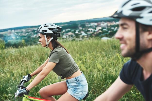 Молодая пара катается на велосипеде на толстых байках и в шлемах крупным планом