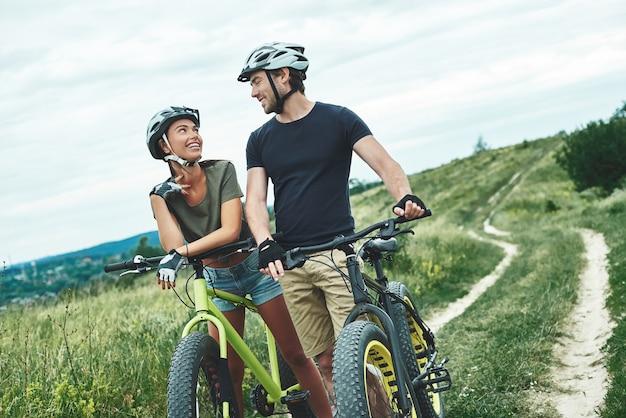 Молодая пара флиртует друг с другом и катается на фэтбайках в шлемах