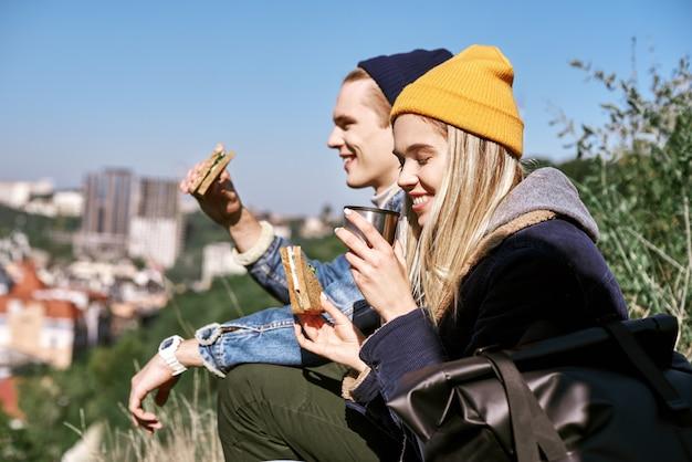 若いカップルが町の近くの丘でピクニックをしている