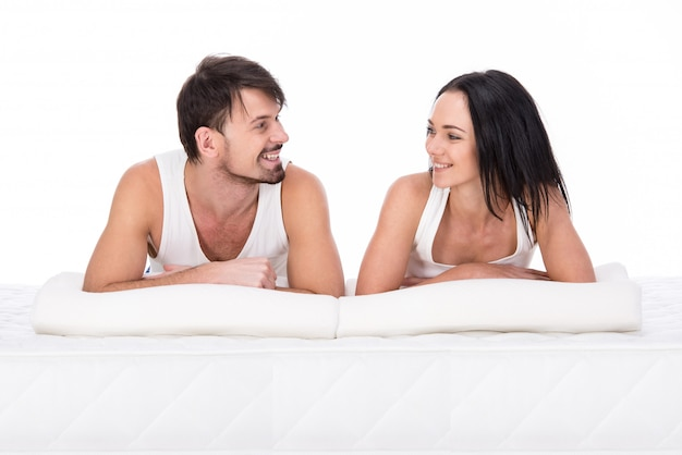 Young couple are lying on the mattress together.