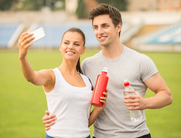 Young couple are making selfie photo on stadium.