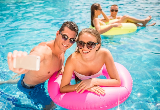 Young couple are making selfie while having fun in pool.