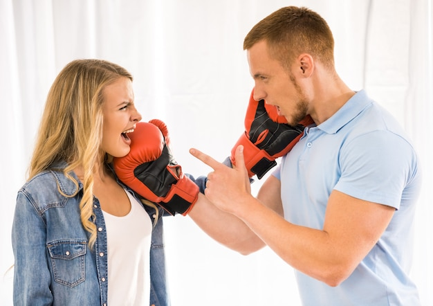 Young couple are quarreling and using boxing gloves.