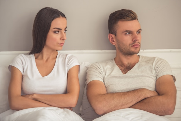 Young couple are sitting with folded arms in bed