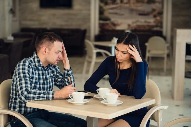 카페에서 주장하는 젊은 부부. 그녀는 충분했고 남자 친구는 사과하고 있습니다. 관계 문제.