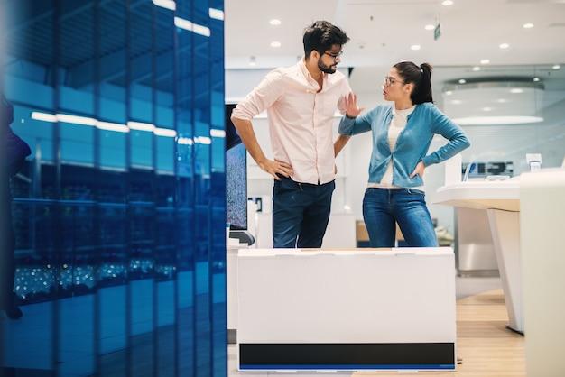 Молодая пара спорит в магазине электроники с коробкой мультфильма перед новой электроникой.